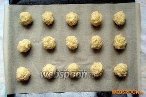 Разогрейте духовку до 180 °С. Застелите противень пекарской бумагой и выкладывайте печенье на небольшом расстоянии друг от друга.