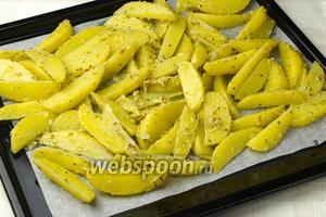 Выстелить противень пергаментной бумагой. Выложить на него картофельные дольки и запекать в разогретой до 200 °С духовке 30-40 минут до образования золотой корочки.