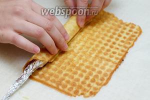 Выложить вафлю на салфетку или пергамент и быстро свернуть в трубочку (когда вафля остынет, она станет хрупкой). Использую для этого толстый карандаш, завёрнутый в несколько слоёв фольги.
