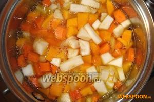 Затем добавить кубики тыквы, корня сельдерея и моркови. Всё смешать, томить 5 минут. Затем добавить кипячёной воды столько, чтобы она смогла покрыть овощи на 2 см сверху. Закрыть кастрюлю крышкой, и на медленном огне оставить варить овощи 20 минут.