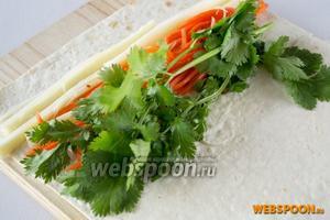Под край лаваша уложить сыр, корейскую морковку и кинзу. Желательно соблюдать очередность.
