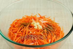 Добавить в морковь все специи и выдавленный через пресс чеснок, затем всё хорошо перемешать и пожать руками.