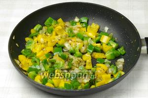 На той же сковороде обжарьте сначала лук со специями (сухой орегано и сладкая паприка) 3 минуты, а после добавьте перец и обжаривайте ещё 5 минут.