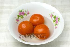 Сделайте надрезы на помидорах и обдайте их кипятком. Затем удалите с них кожицу.