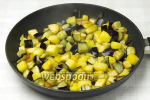 Добавить к картофелю баклажаны и обжаривать ещё 5-8 минут. Обжаривайте овощи на сильном огне, так они сохранят свою структуру.