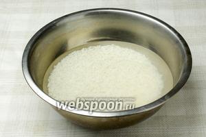 Рис промыть, пока вода не станет прозрачной. Залить водой и оставить на 30 минут. После воду слить и ещё раз промыть рис.