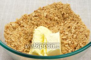 Печенье измельчить в крошку и добавить размягчённое сливочное масло (если масло твёрдое, то его можно растопить на водяной бане).