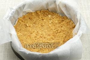 Разъёмную форму застелить пергаментом и выложить печенье в корж. Поставить заготовку в холодильник минимум на 30 минут.