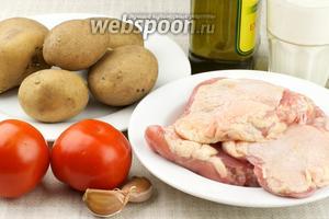 Для приготовления блюда понадобится 5-6 куриных бёдер, картофель, помидоры, кефир, оливковое масло и специи.