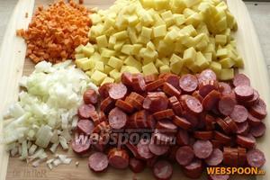 Почистить и порезать кубиками картофель, морковь и лук. Охотничьи колбаски порезать кружочками.