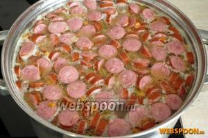 Когда горох станет мягким, добавить морковь, лук и колбаски, после чего варить ещё 10 минут.