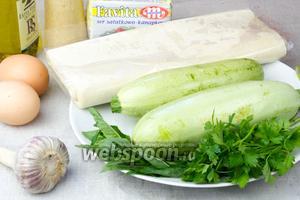 Чтобы приготовить такой тарт возьмите: лист слоёного теста, кабачки небольшого размера, сыр фета, яйца, чеснок, специи, оливковое масло и зелень.