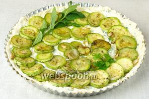 В форму выложить жаренные кабачки и украсить зеленью. Выпекать в разогретой до 180 °С градусов духовке 35-40 минут.