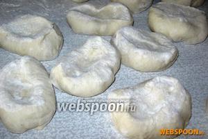 На посыпанном мукой столе или доске разделываем тесто на одинаковые кусочки, которые раскатываем скалкой и формуем пирожки.