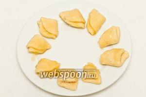 Теперь ещё раз макаем половинки одной стороной в сахар и складываем их пополам, чтобы получились треугольнички.