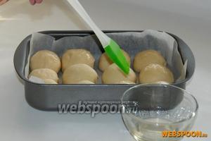 Форму для запекания укладываем пергаментом. Помещаем получившиеся шарики в форму и смазываем поверхность заготовок небольшим количеством растительного масла. Оставляем пампушки ещё на 30 минут в тёплом месте. После расстойки, выпекаем пампушки в духовке при 180 °С 25-30 минут.