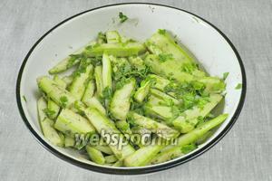 Зелень кинзы помыть, просушить и мелко нарезать. Смешать с кабачками, полить их маслом и оставить на 5 минут мариноваться под крышкой.