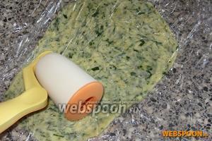 Сырную массу выложить между двумя слоями плёнки и раскатать при помощи скалки в тонкий пласт.