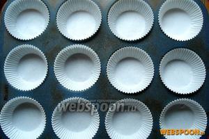 Тем временем в форму для маффинов выложите бумажные формочки (их смазывать не нужно) или смажьте саму форму сливочным маслом.