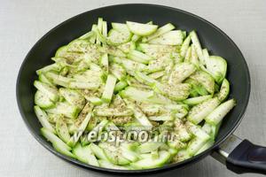 В разогретую сковороду с добавлением масла выложить кабачки и присыпать орегано, перцем, солью. Обжаривать с одной стороны 3-5 минут на среднем огне.