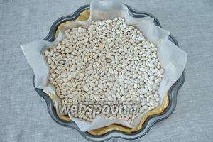 Наколоть тесто вилкой в нескольких местах. Выложить поверх теста бумагу для выпечки, наполнить фасолью(это груз для коржа). Запечь корж в разогретой духовке в течение 15 минут при температуре 200 °С. Груз-фасоль высыпать.