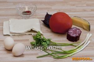 Для 2 порций яичницы в тесте нам потребуется: 2 квадрата слоёного теста, 2 яйца, половинка спелого помидора, несколько кусочков колбасы, сыр, петрушка, базилик, зелёный лук, чайная ложка горчицы в зернах, соль и специи, чёрный и сладкий молотый перец. Пока готовим ингредиенты, включаем духовку (она должна нагреться до 180 °С).