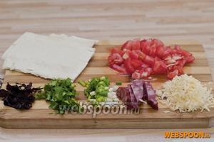 Тесто делим на порционные куски, с помидора снимаем шкурку и режем кубиками, колбасу нарезаем продолговатыми ломтиками, петрушку, лук и базилик мелко режем, сыр трём на мелкой тёрке.