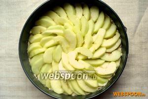 Достать форму из духовки. Выложить на тесто яблоки и вернуть в духовку. Температуру нужно снизить до 180 °С. Выпекать до готовности, от 30 до 50 минут (готовность проверить спичкой). В процессе выпечки, при необходимости, форму сверху прикрыть фольгой.