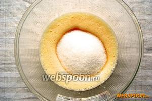 Всыпать к яйцам 1 стакан сахара и взбивать до пышной белой массы.
