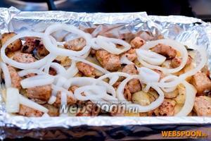 В форму с картошкой выкладываем мясо, выливаем масло, которое осталось в сковородке. Выкладываем колечки лука.