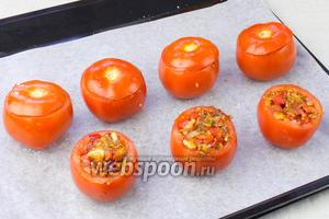 Начинить помидоры овощами и накрыть крышечками. Отправить запекаться в разогретую до 180 °С духовку на 35-35 минут.