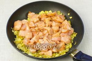 К луку добавить куриное филе, перемешать и обжаривать, пока курица не станет матовой. Это займёт приблизительно 5-7 минут.
