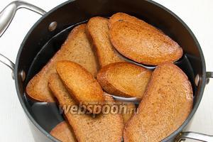 Воду немного охлаждаем и кладём в неё жареный хлеб.