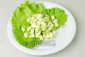 На тарелку выложить салатные листья, а сверху положить авокадо.