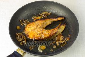 Маринованную рыбу обжарить в раскалённой сковороде с добавлением масла. Переворачивать как можно меньшее количество раз. Когда рыба подрумяниться добавить лук и обжаривать 3-5 минут. Готовую рыбу подавать с гарниром или салатом из свежих овощей.