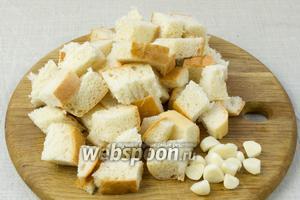 Хлеб порезать на кубики. Чеснок очистить и крупно порубить ножом.