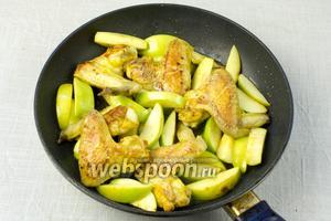 Перемешать мясо и яблоки так, чтобы куриные крылья были сверху. Уменьшить огонь до минимума, накрыть крышкой и жарить 5 минут.