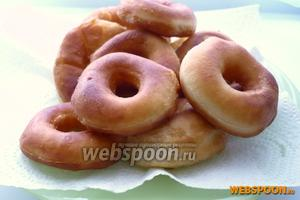 Жареные пончики выложить на салфетку, для того чтобы впиталось лишнее масло. Посыпать сахарной пудрой и подавать горячими.