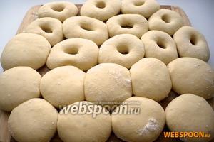 Выложите пончики на посыпанную мукой доску на достаточном расстоянии друг от друга и оставьте расстаиваться, до тех пор, пока они не увеличатся в объёме в 2 раза.