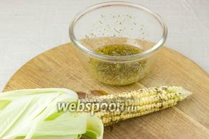 Намажьте початки кукурузы маслом с травами.