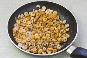 Затем выдавить чеснок, добавить 1 столовую ложку оливкового масла и 2 столовые ложки соевого соуса. Жарить креветки 5-7 минут.