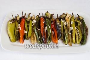 Печёные перцы вынуть из духовки и выложить на блюдо. Посыпать рубленым чесноком. Залить соусом.