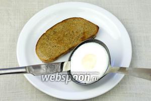 Когда яйцо станет абсолютно белым, пройдитесь по краям ножом и отделите его от стенки половника. Яйцо положить на тост.