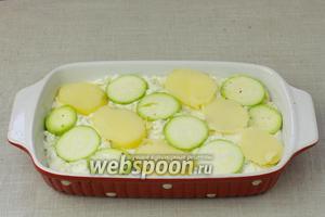 На тесто выложить кружочки кабачка и картофеля. Накрыть фольгой и оставить ещё на 30 минут. По желанию, украсить зеленью. Затем отправить запекаться в разогретую до 180 °С духовку на 50 минут.