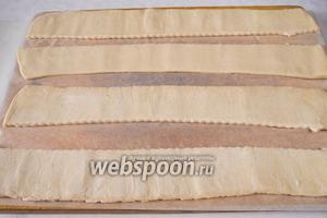 Разложить тесто на пергаментной бумаге для выпечки. Разрезать листы теста на полоски шириной 6-7 см. Если получится, соединить все полосы в одну общую ленту. Закрутить, присыпая мукой.