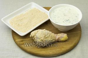 Каждую куриную ножку окунуть сначала в йогуртовый кляр, а затем обвалять в панировочных сухарях.