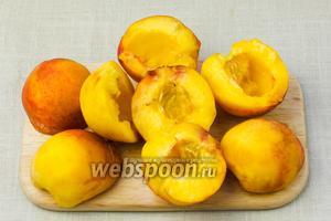 Персики помыть, разрезать на половинки и вынуть косточки.