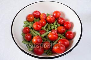 Поместить стручки фасоли и помидоры в миску. Посолить, влить 1 ст. л. оливкового масла. Перемешать.