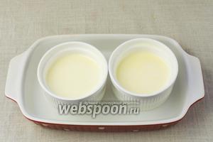 Влить жидкость в формочки и поставить их в форму наполненную водой так, чтобы она доходила до середины креманок.   Отправить запекаться в нагретую до 180 °C духовку на 25 минут.
