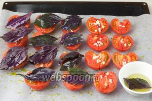 Помидоры посыпать рубленным чесноком. Каждый листик базилика смочить в оливковом масле и выложить на помидоры. Томаты запекать 50 минут при при температуре  190 ˚С.